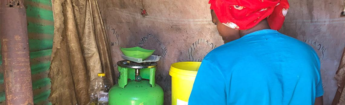 Woman cooking in a settlement in Soweto, South Africa